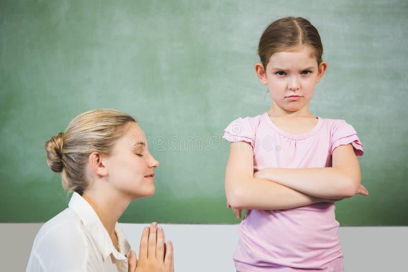 Menina de desculpa do professor fêmea na sala de aula foto de stock