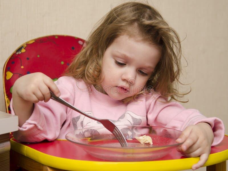 A menina de dois anos come o assento na tabela na cozinha. A menina come com uma forquilha. imagem de stock