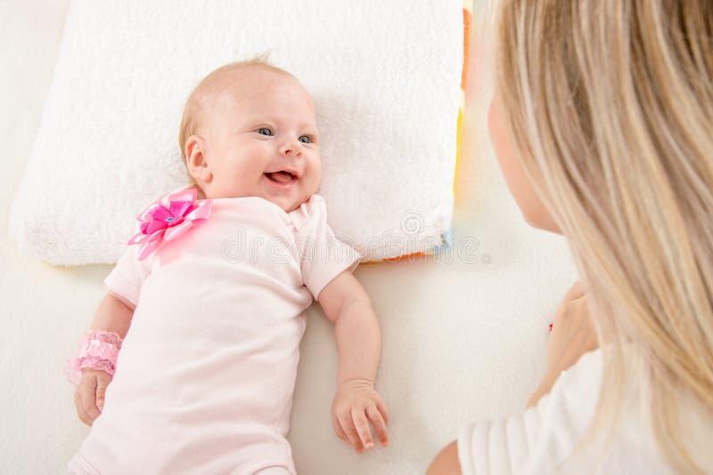 Menina de dois meses feliz que olha a mãe fotografia de stock royalty free