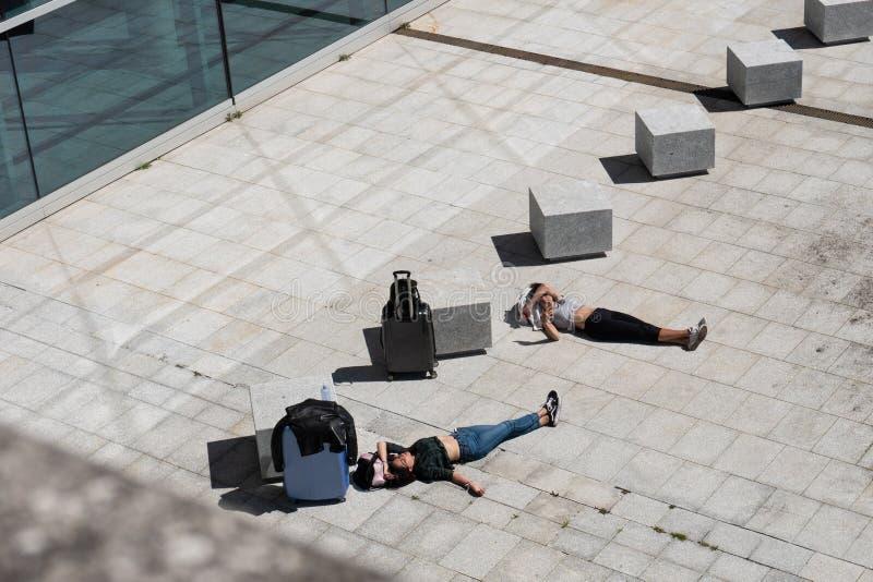Menina de dois viajantes que encontra-se na espera da pedra de pavimentação e que tem um banho do sol imagens de stock royalty free