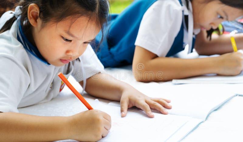 A menina de duas irmãs escreve aos escrita-livros A decisão das lições a menina estabelece a tiragem da imagem imagens de stock royalty free