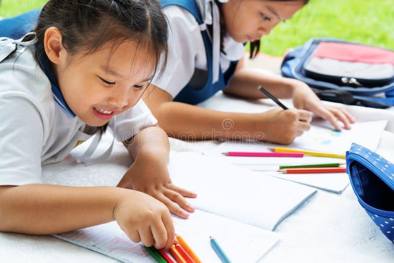A menina de duas irmãs escreve aos escrita-livros A decisão das lições a menina estabelece a tiragem da imagem foto de stock