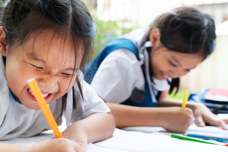 A menina de duas irmãs escreve aos escrita-livros A decisão das lições a menina estabelece a tiragem da imagem imagens de stock