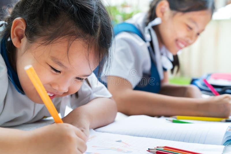 A menina de duas irmãs escreve aos escrita-livros A decisão das lições a menina estabelece a tiragem da imagem fotos de stock royalty free
