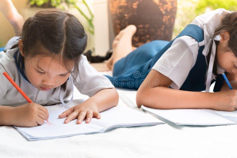 A menina de duas irmãs escreve aos escrita-livros A decisão das lições a menina estabelece a tiragem da imagem fotos de stock