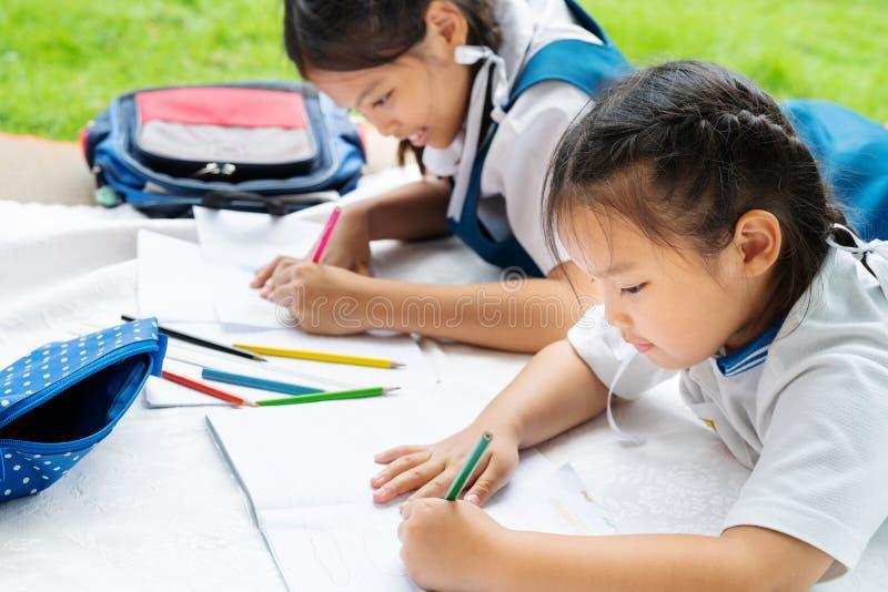 A menina de duas irmãs escreve aos escrita-livros A decisão das lições a menina estabelece a tiragem da imagem foto de stock royalty free