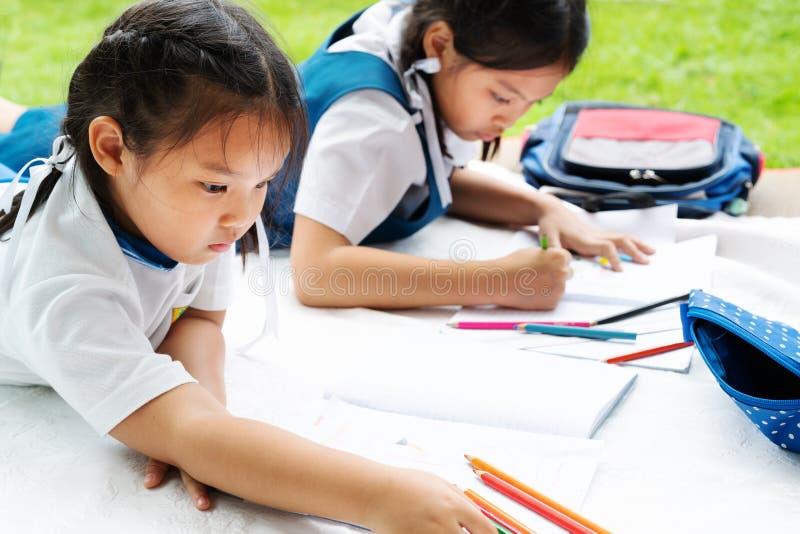 A menina de duas irmãs escreve aos escrita-livros A decisão das lições a menina estabelece a tiragem da imagem imagem de stock royalty free