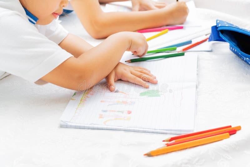 A menina de duas irmãs escreve aos escrita-livros A decisão das lições a menina estabelece a tiragem da imagem fotografia de stock royalty free