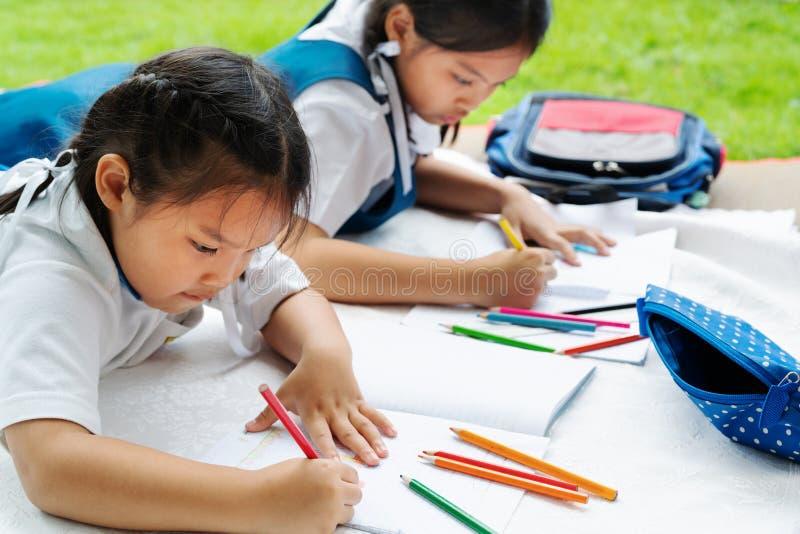 A menina de duas irmãs escreve aos escrita-livros A decisão das lições a menina estabelece a tiragem da imagem imagem de stock