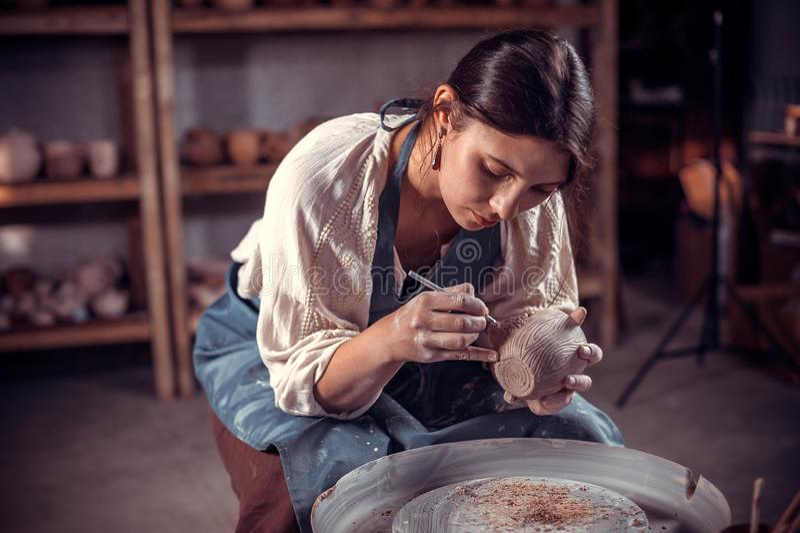 A menina de encantamento do ceramist está trabalhando na roda da cerâmica handmade fotografia de stock
