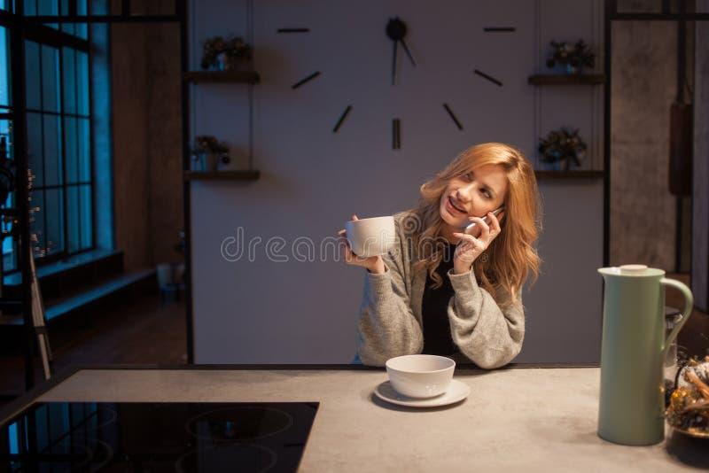 Menina de encantamento na cozinha na manhã Fala no telefone e ter a jovem mulher do café da manhã A com a caneca em suas mãos imagem de stock