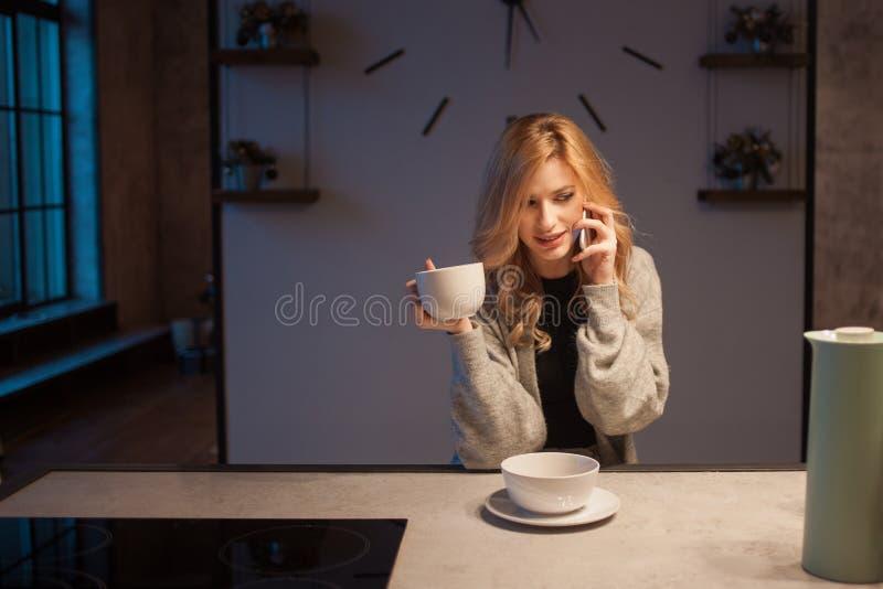 Menina de encantamento na cozinha na manhã Fala no telefone e ter a jovem mulher do café da manhã A com a caneca em suas mãos foto de stock royalty free