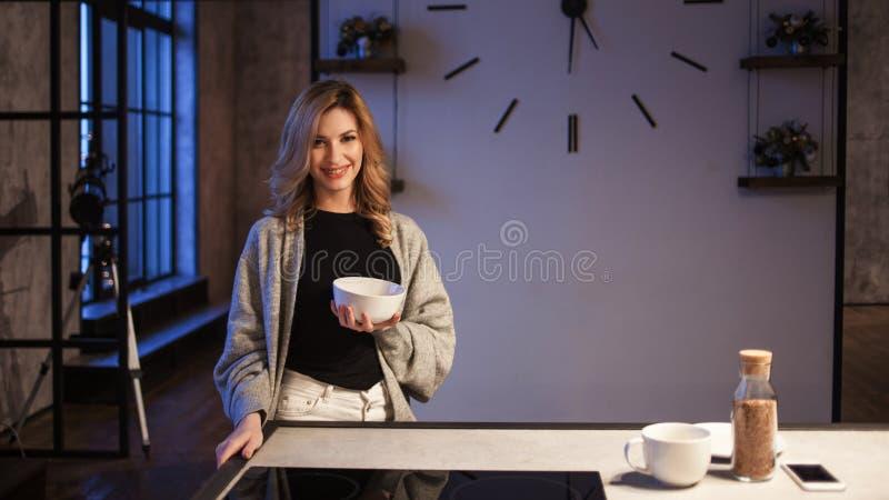 Menina de encantamento na cozinha na manhã Fala no telefone e ter a jovem mulher do café da manhã A com a caneca em suas mãos foto de stock