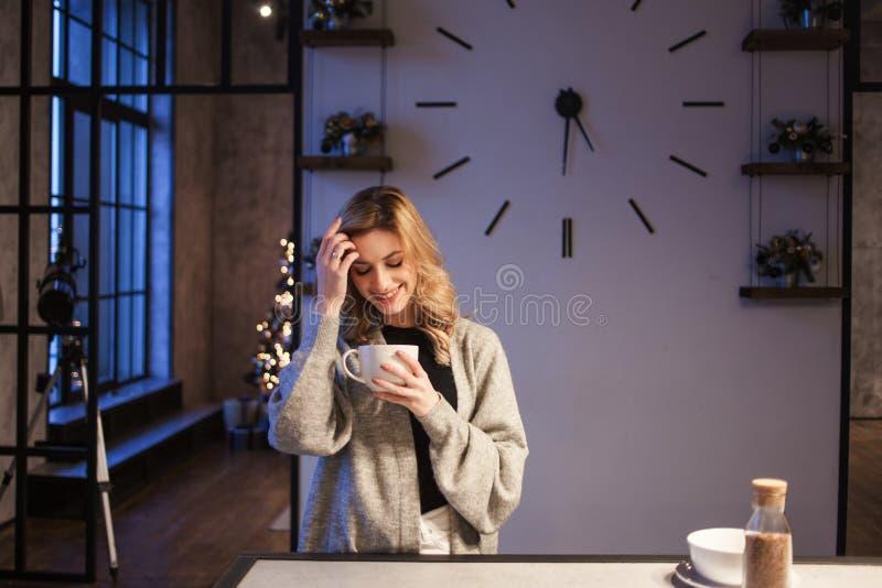 Menina de encantamento na cozinha na manhã Fala no telefone e ter a jovem mulher do café da manhã A com a caneca em suas mãos fotos de stock