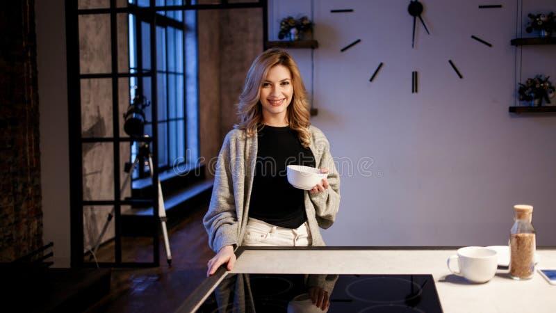 Menina de encantamento na cozinha na manhã Fala no telefone e ter a jovem mulher do café da manhã A com a caneca em suas mãos imagens de stock