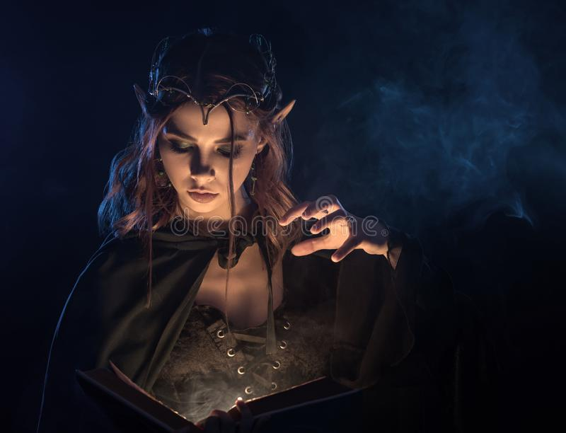 Menina de encantamento no casaco esmeralda que pratica a habilidade mágica fotografia de stock