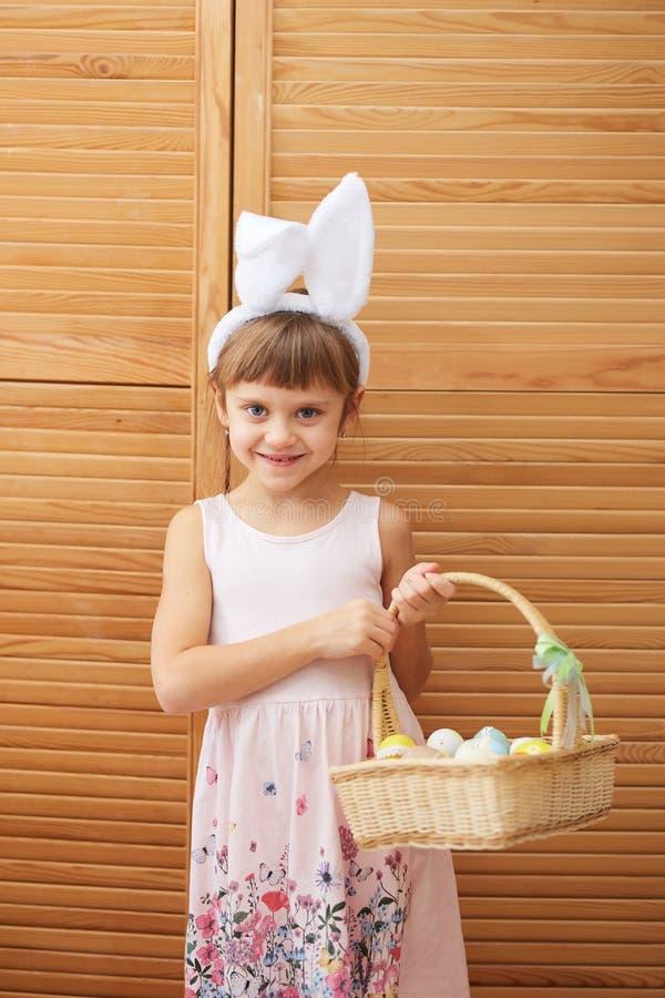 A menina de encantamento no vestido com as orelhas de coelho brancas em sua cabeça guarda uma cesta com os ovos tingidos no fotografia de stock