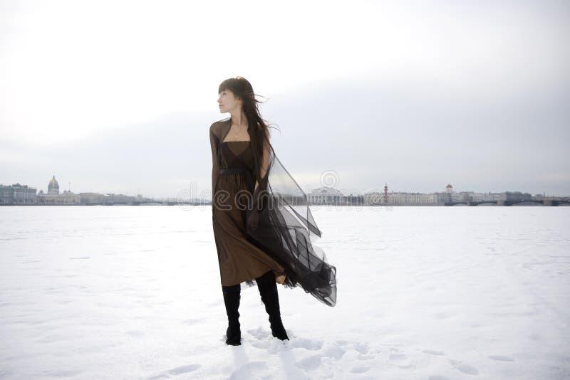 Menina de encontro a um fundo da neve e da cidade. imagens de stock royalty free