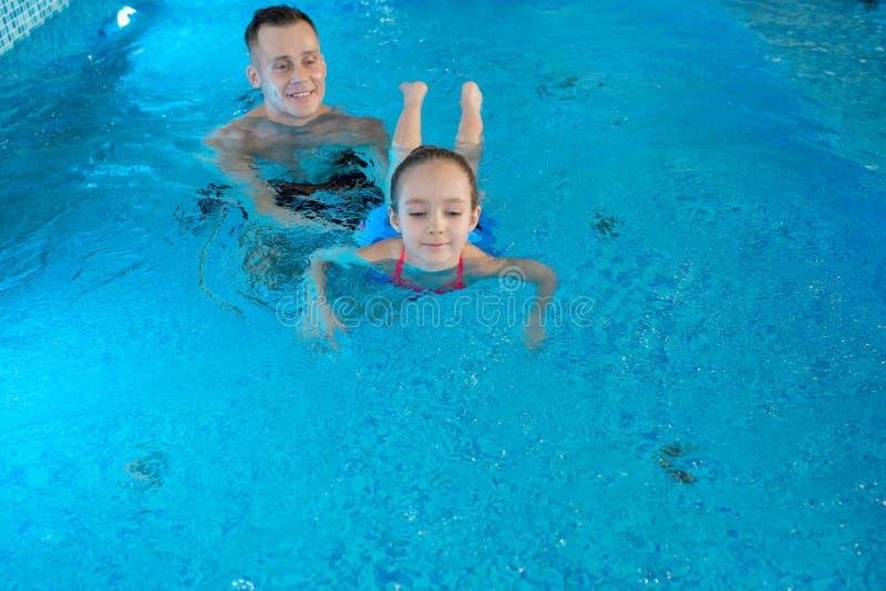 Menina de ensino do treinador pessoal a nadar imagens de stock royalty free