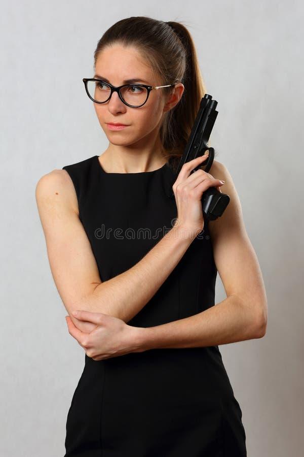 Menina de escritório no vestido preto nos vidros com uma arma foto de stock