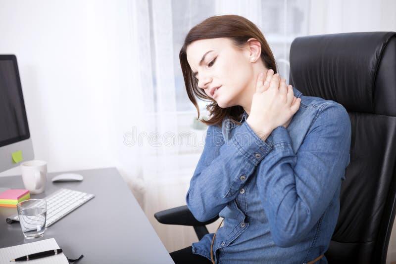 Menina de escritório nova cansado que guarda seu pescoço imagens de stock royalty free