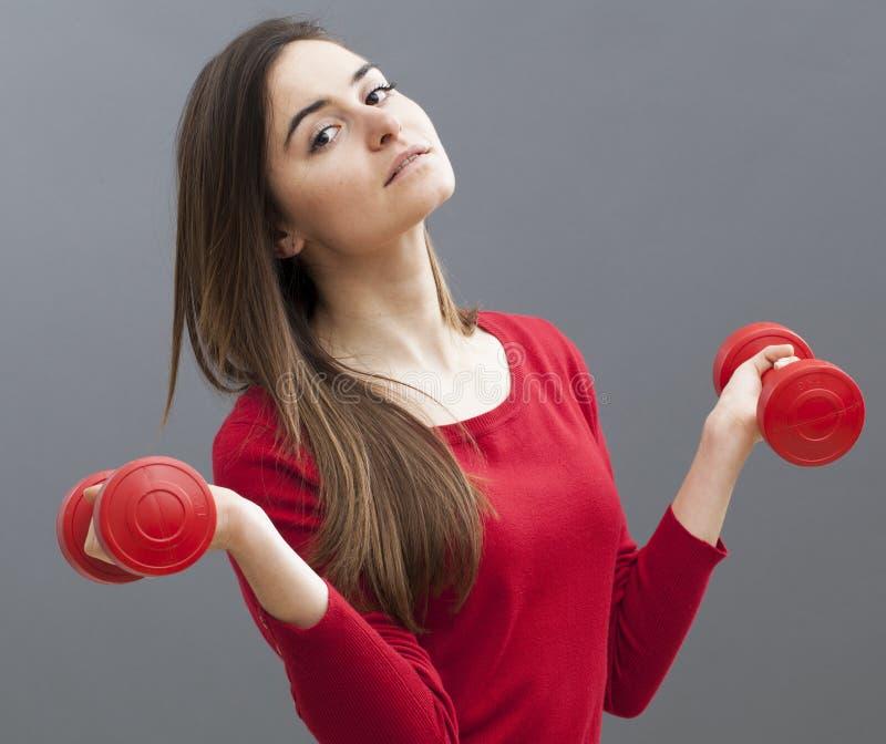 Menina de escritório 20s relaxado que guarda sinos mudos para os braços tonificados e o bem-estar imagem de stock
