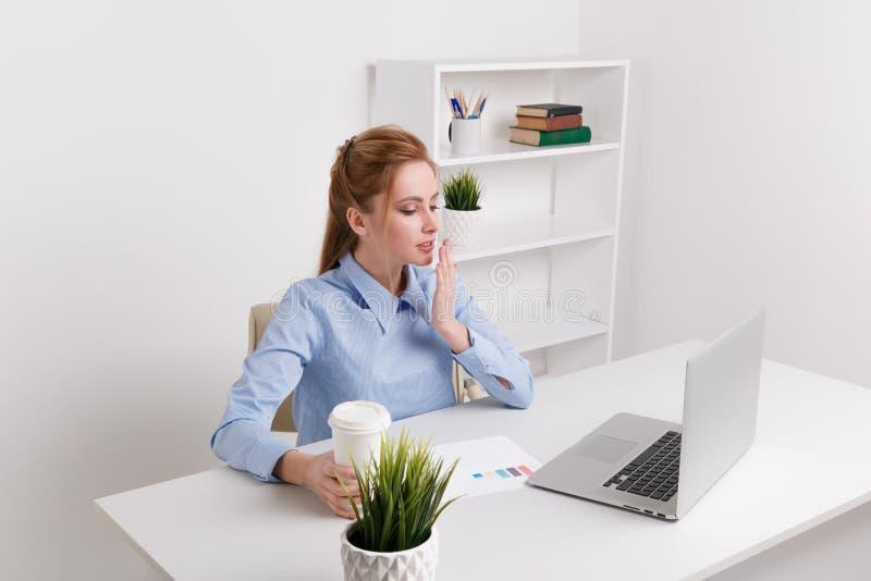 Menina de escrit?rio nova que senta-se em seu sentimento do local de trabalho sonolento foto de stock royalty free