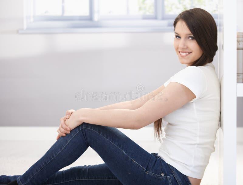 Menina de faculdade feliz que senta-se no assoalho imagem de stock