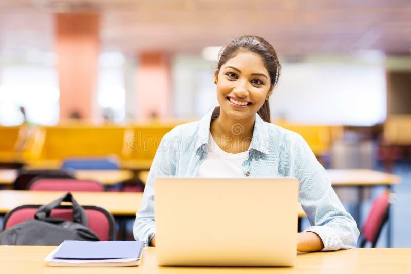 Menina de faculdade que usa o portátil imagem de stock