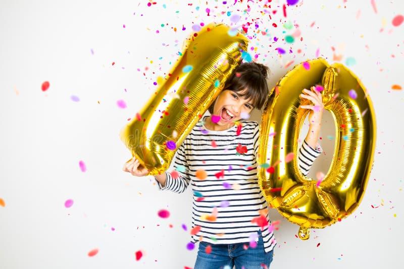 Menina de festa de anos dez com balões e confetes dourados foto de stock