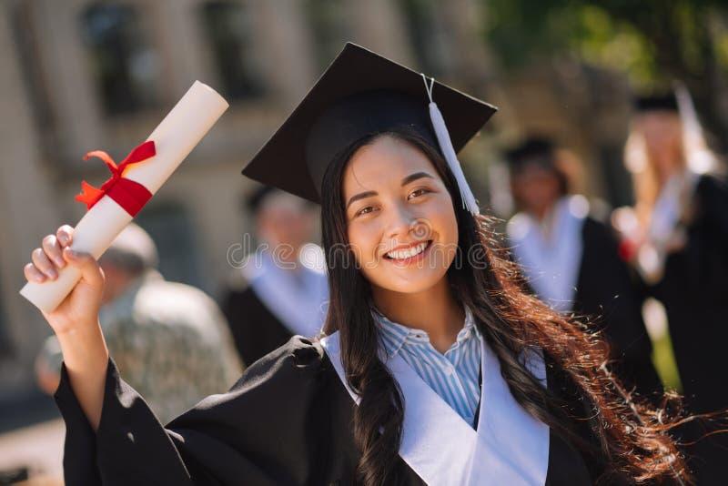 Menina de graduação orgulhosa que mostra seu diploma no terreno imagem de stock royalty free