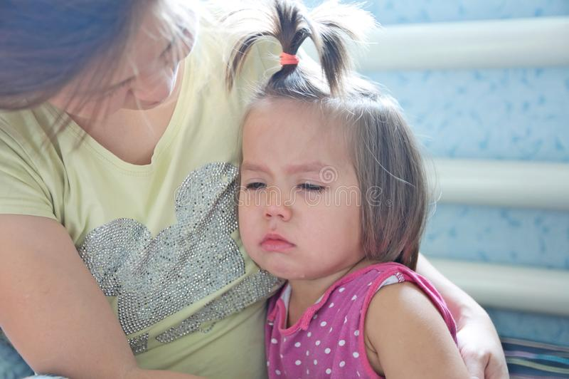 Menina de grito da terra arrendada da mãe acalmando para baixo a criança Chorar do rasgo imagem de stock royalty free