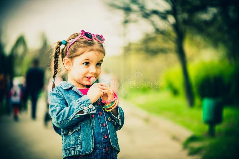 Menina de Haappy com os doces exteriores no parque fotografia de stock