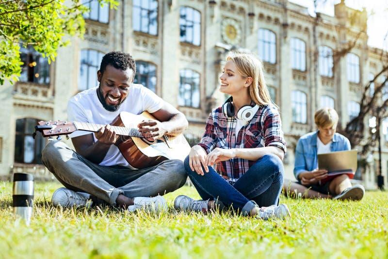 Menina de irradiação que escuta seu amigo que joga a guitarra fotos de stock royalty free