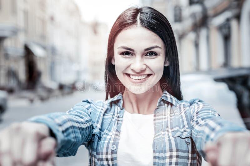 Menina de irradiação que guarda as mãos e que sorri na câmera foto de stock