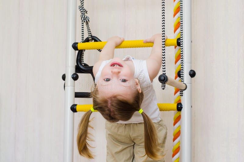 A menina de Ittle pendura nas escadas de cabeça para baixo foto de stock royalty free