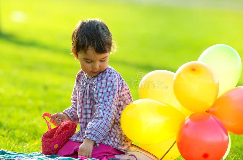 Menina de Ittle que senta-se na grama com os balões na mola fotografia de stock