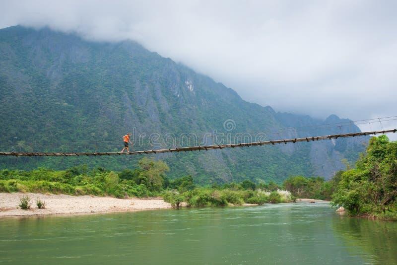 A menina de Laos na roupa tradicional do lao vai em uma ponte de madeira ov imagem de stock
