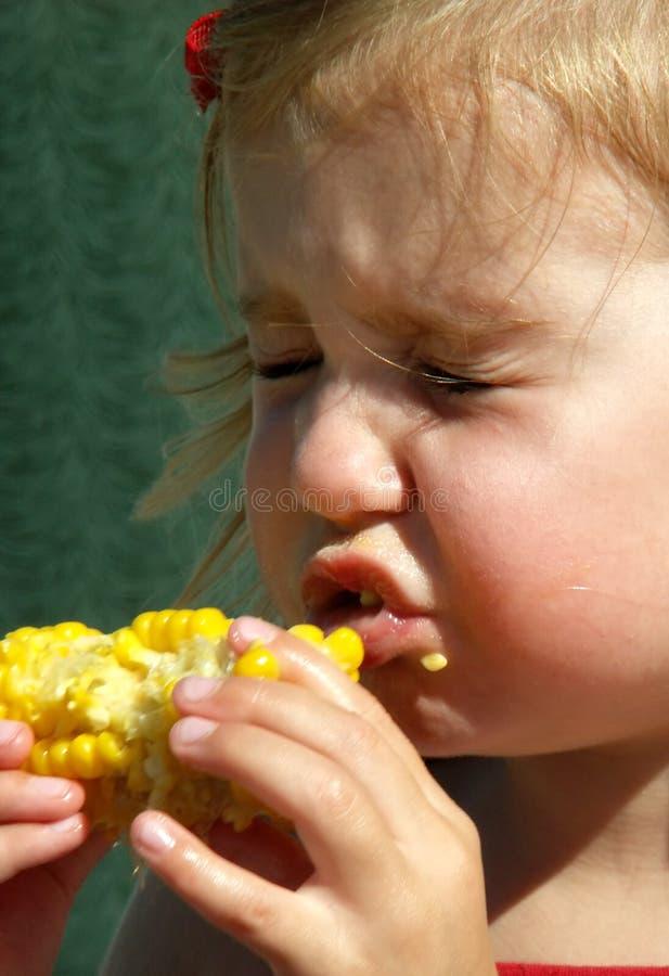 Menina de Litle que come a espiga de milho foto de stock