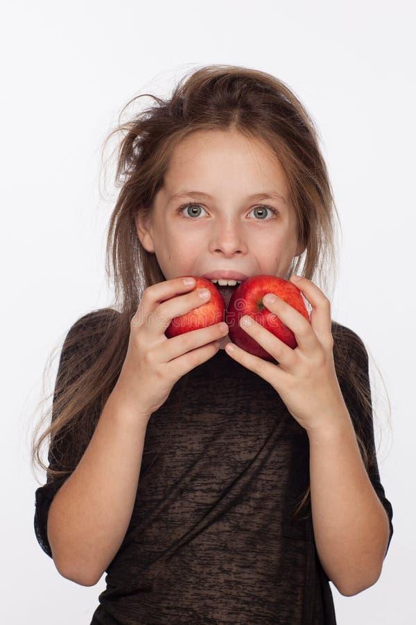 Menina de oito anos emocional bonita com maçãs Sessão de foto no estúdio A menina está vestindo uma blusa preta fotos de stock