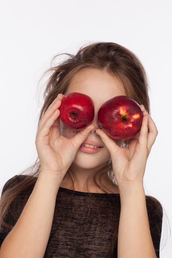 Menina de oito anos emocional bonita com maçãs Sessão de foto no estúdio A menina está vestindo uma blusa preta imagens de stock royalty free