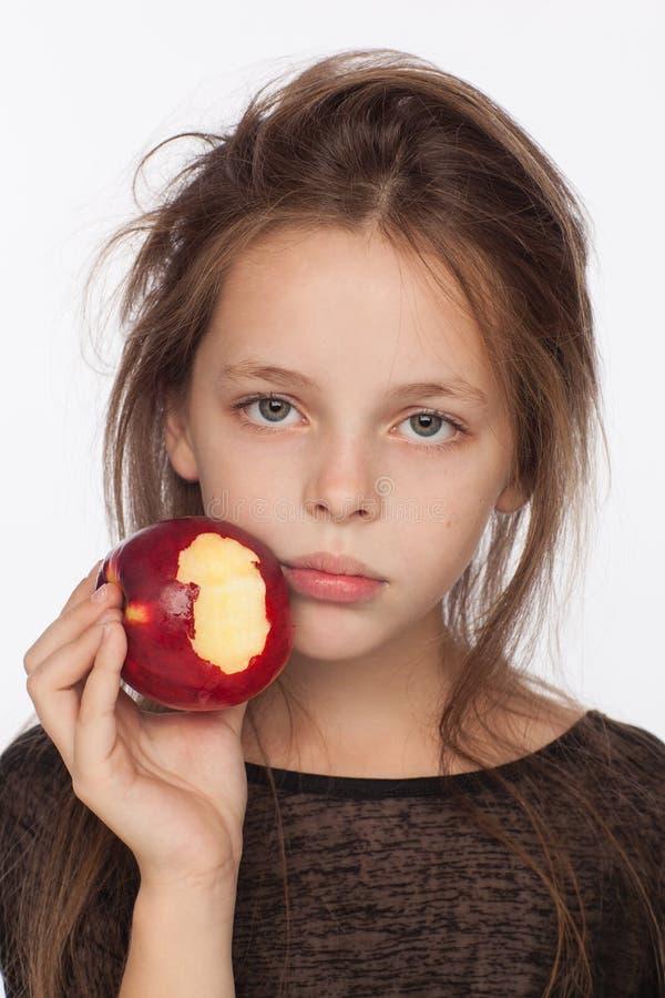Menina de oito anos emocional bonita com uma maçã Sessão de foto no estúdio A menina está vestindo uma blusa preta fotos de stock