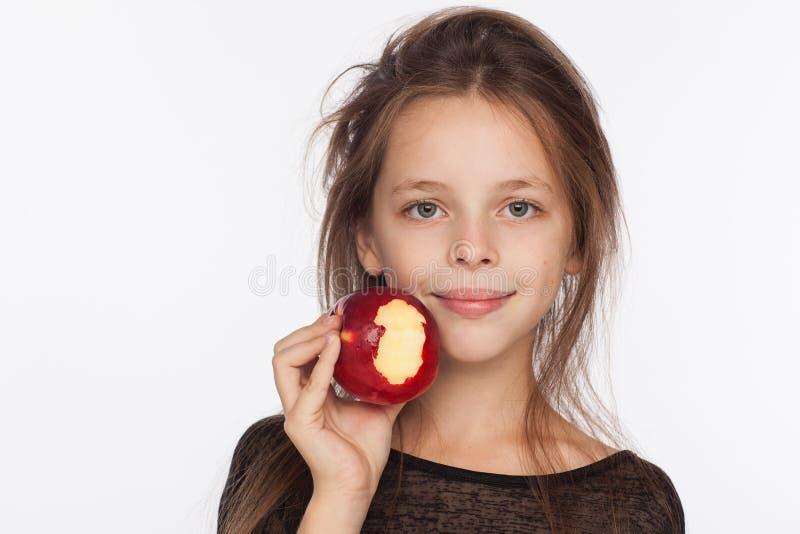 Menina de oito anos emocional bonita com uma maçã Sessão de foto no estúdio A menina está vestindo uma blusa preta imagens de stock royalty free