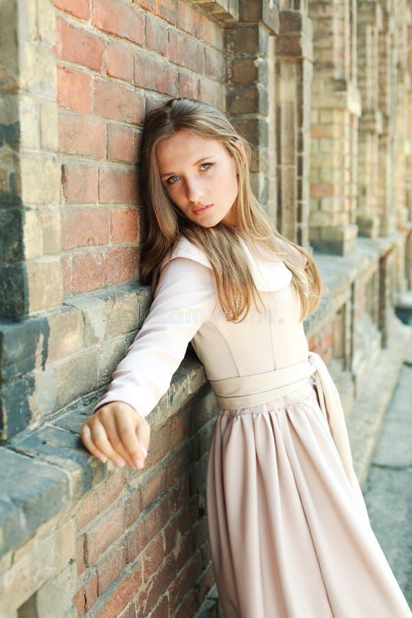 Menina de olhos azuis apaixonado perto da parede de tijolo antiga imagem de stock royalty free