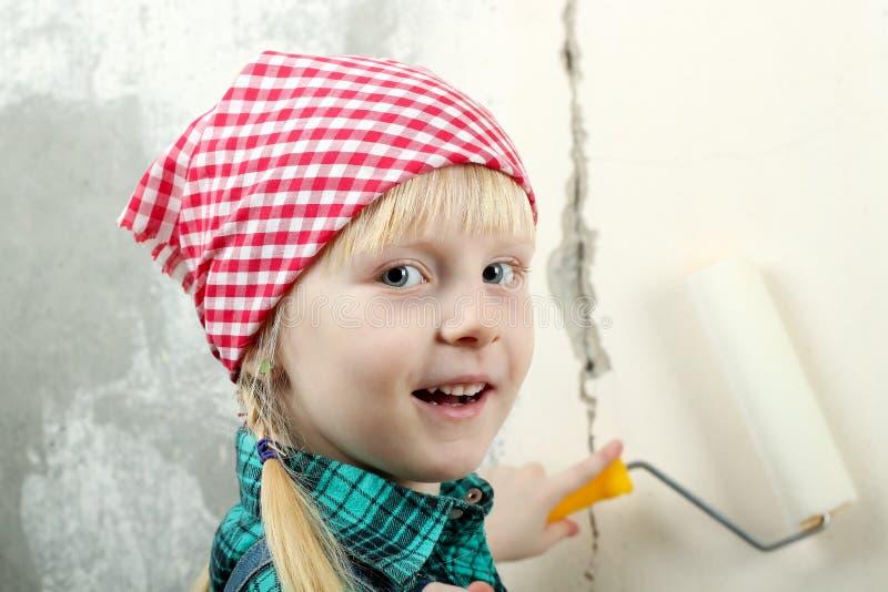 Menina de olhos azuis loura que faz reparos no apartamento imagens de stock