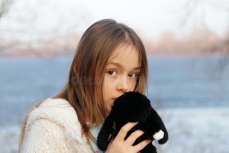 Menina de olhos castanhos pequena bonita que olha a câmera que guarda seu brinquedo macio foto de stock