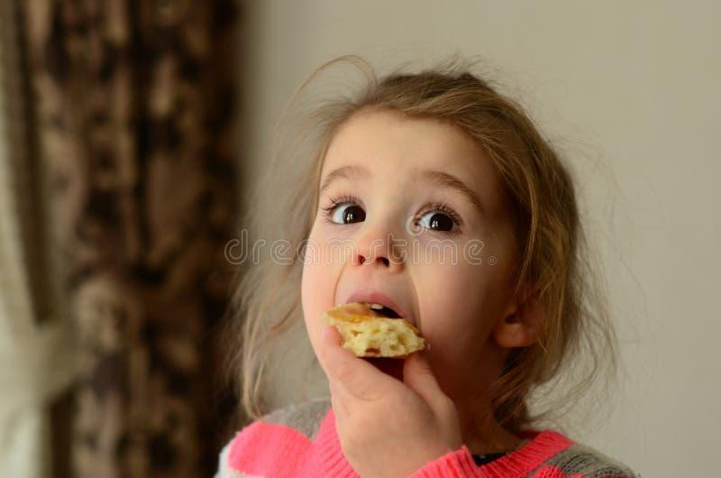 A menina de olhos castanhos remove a uma mordida um bolo fotos de stock