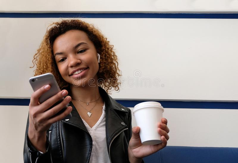 Menina de pele escura bonita feliz que guarda um vidro branco em sua mão e que olha no telefone Um fone de ouvido sem fio na orel fotografia de stock
