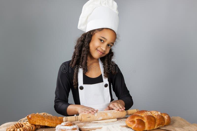 A menina de pele escura pequena rola a massa A criança aprende cozinhar Chapéu da roupa e do cozinheiro chefe imagem de stock
