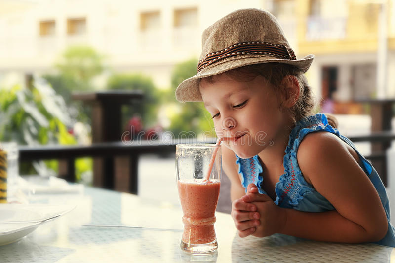 Menina de pensamento bonito da criança que bebe o suco saboroso foto de stock royalty free